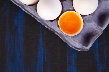 Natural organic chicken eggs in cardboard package on blue background. Copy space. Top view. Flat lay.
