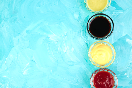Set of different sauces. Sauces ketchup, mustard, mayonnaise, wasabi, soy sauce in little bowls on blue background Stock Photo