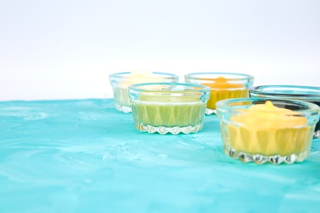 Set of different sauces. Sauces ketchup, mustard, mayonnaise, wasabi, soy sauce in little bowls on blue background Banco de Imagens