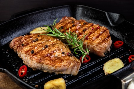Grilled pork steak in grill pan with rosemary, pepper chilli and ginger on wooden board.