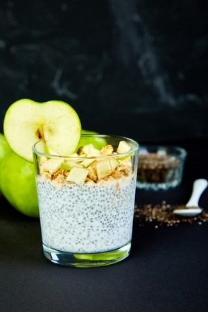 Healthy chia pudding with apples and granola in glass on black background. Vegan creamy breakfast.Detox and healthy superfoods breakfast concept.