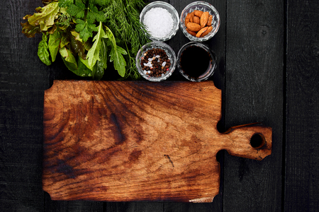 Ingredient for salad - mix leaf on wooden cutting board. Lettuce, mangold, parsley, dill, arugula, almond, salt, tasty, balsamic, pepper. Healthy diet Clear food Vegan Flat lay Copy space  Stockfoto