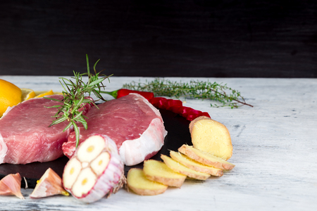 Raw pork meat on black slate plate with spice ingredient - rosemary, ginger, chilli pepper, onion. Standard-Bild