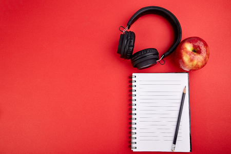 Black Headphones and apple with notebook, note on red background. Flat lay. Top view. Copy space.