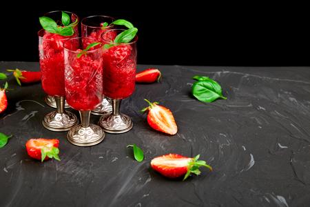 Summer refreshing strawberry sorbet, slush granita drink in serving glasses. Healthy low calorie summer treat, dessert. Iced Cocktail on black background.