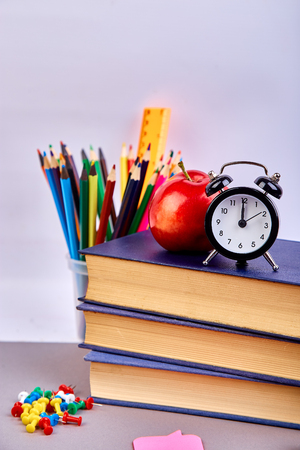 Back to school supplies. Books and red apple on green background. Still life with alarm clock. Copy space.