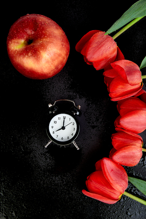 Black alarm clock near bouquet red tulips and red apple on black background.Mother or Woman  Day. Greeting Card. Good Morning breakfast. Copy space. Spring.