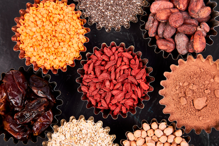 Various superfoods in small bowl on blackbackground. Superfood as chia, raw cocoa bean, goji, chickpeas, lentils. Copy space. Flat lay.