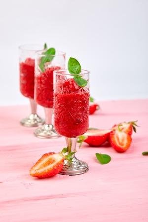 Summer refreshing strawberry sorbet, slush granita drink in serving glasses. Healthy low calorie summer treat, dessert. Iced Cocktail on pink background