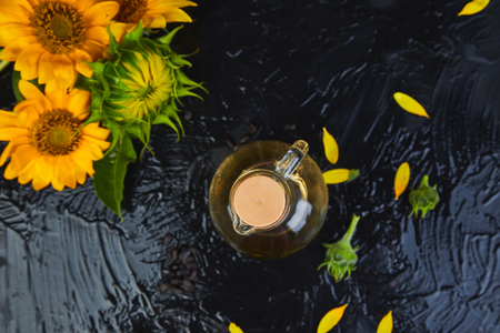 Sunflower oil in glass jar, sunflower seeds and fresh flowers on black table background. Bio and organic product concept. Space for text.