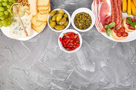 Italian antipasti wine snacks set. Antipasto catering platter with jerky, salami, cheese , grapes, olives, pickles, Prosciutto di Parma with melon, Brushettas on  grunge grey background. Italian food. Mediterranean.  Falt lay. Copy space.