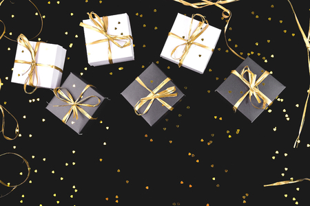 Black and white gift boxes with gold ribbon on shine background. Flat lay. Copy space Stock Photo