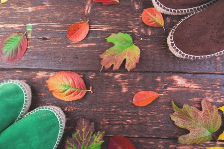 Brown and green man suede boots espadrilles  on wooden background with leaves. Autumn or winter shoes. two pair. Flat lay. Фото со стока