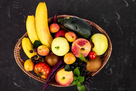 Healthy colorful food selection: fruit, vegetable, superfood,  leaf in basket on dark background. Clean eating. Vegan. Detox. Supermarket product. Assortment Fresh Organic. Natural Concept 写真素材