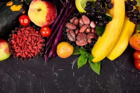 Healthy colorful food selection: fruit, vegetable, seeds, superfood, beans, leaf vegetable on dark background. Clean eating. Vegan. Detox. Supermarket product Assortment Fresh Organic Natural Concept