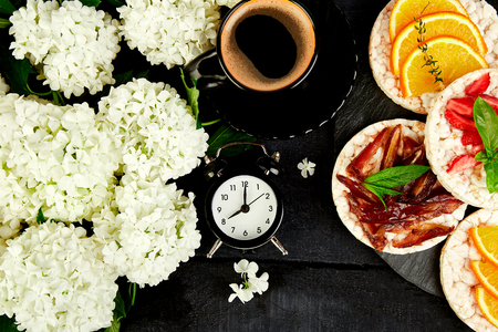 Alarm clock have a good day with a cup of coffee. Good morning, breakfast. Snack with crispbread and fresh fruits on black background. Healthy food concept. Flat lay, top view, copy space Banque d'images