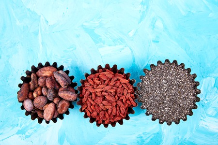 Various superfoods in small bowl on blue background. Superfood as chia, raw cocoa bean, goji. Copy space. Flat lay.