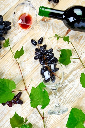 Red wine concept with bottle, glass and grapes on wooden background, top view, flat lay. Wine header image. Wineglasses.