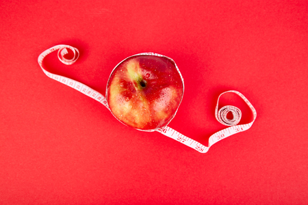 Measuring tape wrapped around a red apple as a symbol of diet on red paper background. Weight loss concept. Diet. Dieting concept. Vegan. Clear food. Healthy. Top view. Minimalism