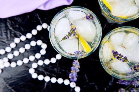 Lavender lemonade with lemon and ice on black background. Detox water. Summer drink. Diet cocktail. Beautiful. Top view. Copy space. 免版税图像