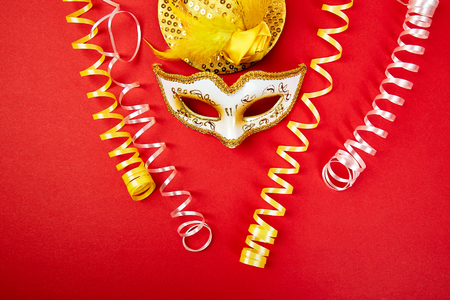 Masque de carnaval jaune et blanc sur rouge