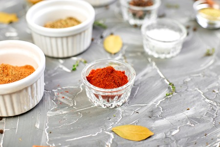 Seasoning background. Spice and herb seasoning with fresh and dried herbs and spices in bowls. Colourful various herbs and spices for cooking on grey background. Copy space. Zdjęcie Seryjne