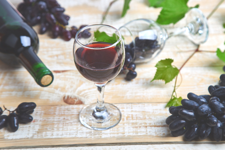 Red wine concept with bottle, glass and grapes on wooden background. Wine header image. Wineglasses.
