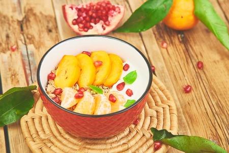 Tropical fruit  smoothies bowl Breakfast homemade granola yogurt pomegranate, tangerine, persimmon on wooden rustic background. healthy organic layered dessert. Diet, vegan food. Top View