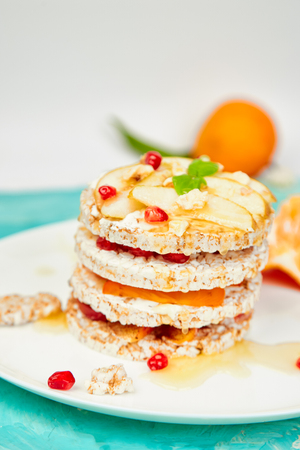 Vegan, diet, organic natural birthday cake with rice crisp bread and tropical fruits on blue background. Easy food. Healthy layered dessert.