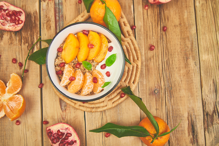 Tropical fruit  smoothies bowl Breakfast homemade granola yogurt pomegranate, tangerine, persimmon on wooden rustic background. healthy organic layered dessert. Diet, vegan food. Top View
