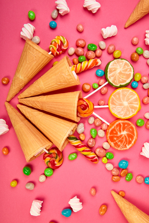 Ice cream waffles cones with colorful candy, sweets jelly, lollipop on stick, scattering of multicolored sweets on pink background. Flat lay, Top view. Copy space.