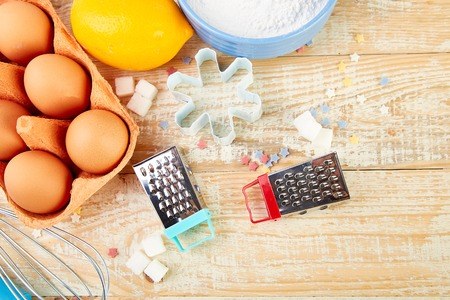 Baking or cooking ingredients - flour, eggs, lemon,  sugar, wooden spoon, rolling pin and different tools on a wooden table background.  Dessert ingredients and utensils.  Bakery frame. Top view, copy space. Flat lay.