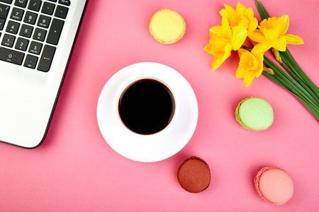 Woman or feminine workspace with laptop, notebook, cup of coffee, macarons, and flowers narcissus on pink table. Top view. Flat lay. Copy space.