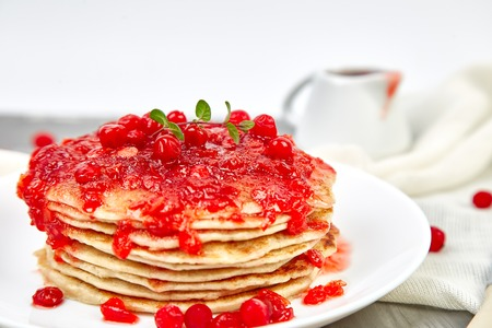 American pancake with jam - berry, viburnum, cranberry on grey background. Homemade pancakes with berry sauce and mint. Healthy breakfast with fresh hot pancakes with berry jam
