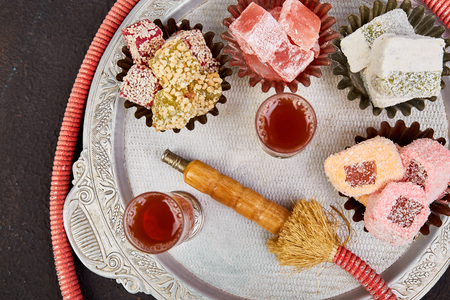 Set of various Turkish delight in traditional silver bowl on metal tray near hookah tube black background Middle Eastern dessert.  Top view. Flat lay. Copy space. 版權商用圖片