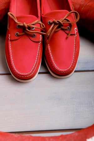 Red boat shoes on wooden background near lifebuoy. Top view. Flat lay. Copy psace. Reklamní fotografie