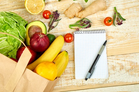Shopping list, recipe book, diet plan. Grocering concept. Full paper bag of different fruits and vegetables,  ingredients for healthy cooking on a wooden background. healthy food.  Diet or vegan food, vegetarian. Top view. Flat lay.