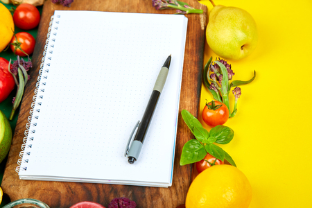Shopping list, recipe book, diet plan. Fresh raw vegetables, fruit and ingredients for healthy cooking. top view, place for text. Diet or vegan food, healthily cooking concept. Flat lay. Notepad for your recipe concept.