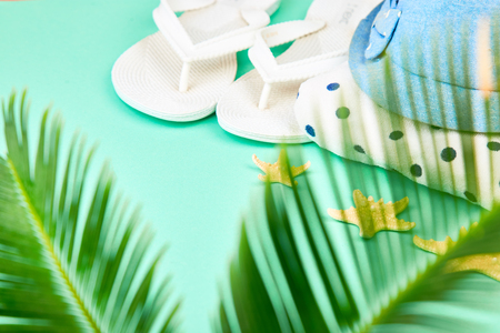 Summer female fashion outfit. Sunhat, white flip flops, polka dot towel, and starfish with tropical palm branches on blue background. Beach, vacation, travel concept, Minimalism.  Flat lay, top view. Copy space. Stock Photo