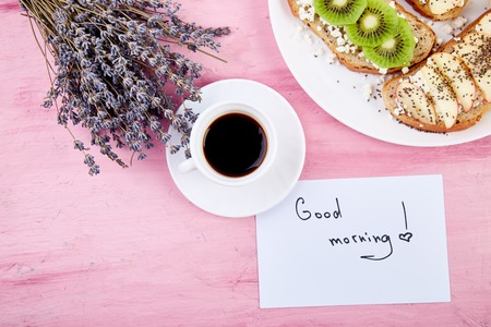 Coffee mug and healthy toasts breakfast  with bouquet of flowers lavender and notes good morning on pink table.