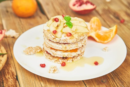 Vegan, diet, organic natural birthday cake with rice crisp bread and tropical fruits on wooden rustic background. Easy food. Healthy layered dessert. 스톡 콘텐츠