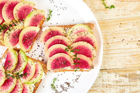 Healthy breakfast toasts from sliced watermelon radish or chinese daikon, chia and cottage cheese on white plate, wooden background. Top view. Copy space.