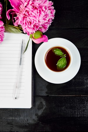 Peony flowers on black background with note or diary and cup of coffee. Planing to do list. Copy space. Flat lay. Empty blank. Woman workplace. Good morning.