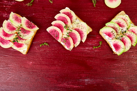 Healthy breakfast toasts from sliced watermelon radish or chinese daikon , chia  and cottage cheese on red background. Top view. Flat lay. Copy space.