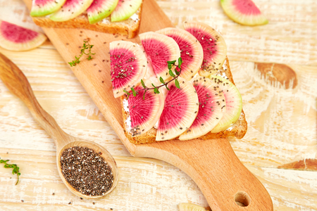 Healthy breakfast toasts from sliced watermelon radish or chinese daikon, chia and cottage cheese on board wooden background. Copy space.  写真素材