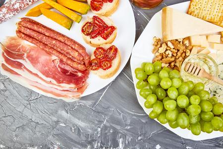Italian antipasti wine snacks set. Antipasto catering platter with, salami, cheese , grapes,, Prosciutto Brushettas on grunge grey background. Italian food. Mediterranean. Falt lay. Copy space 免版税图像