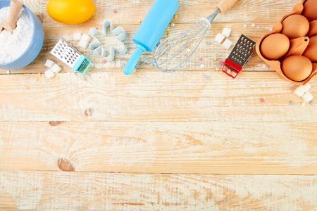Baking or cooking ingredients flour, eggs, lemon, sugar, rolling pin and different tools on a wooden table background. Dessert ingredients and utensils. Bakery frame. Top view, copy space. Flat lay. Standard-Bild