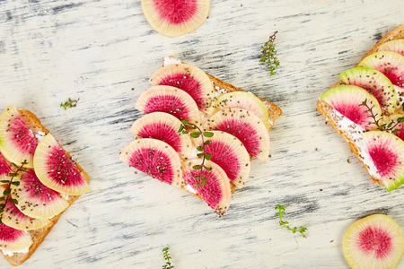 Healthy breakfast toasts from sliced watermelon radish or chinese daikon, chia and cottage cheese on whte background. Top view. Flat lay. Copy space.