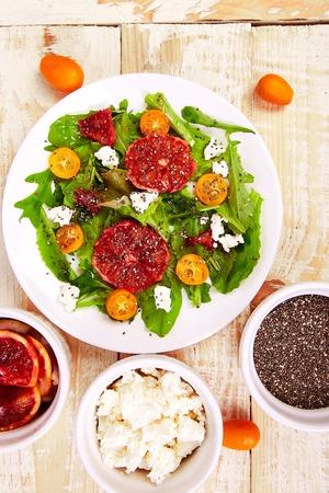 Insalata di agrumi freschi con rucola feta, chia, kumquat e arancia rossa su sfondo blu. Vegano, vegetariano, mangiare pulito, dieta, concetto di cibo. Vista dall'alto, distesi, copia spazio