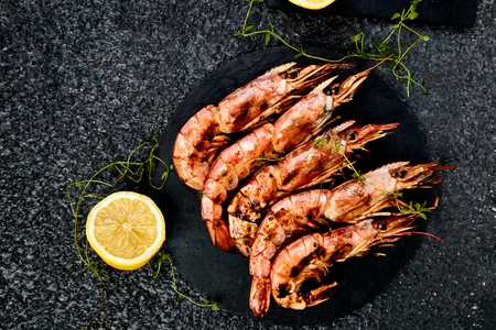 Grilled big tiger shrimps prawns on black slate plate with spices, lemon, fresh herbs on black background, top view. Grilled seafood. Barbecue shrimps. Copy space.